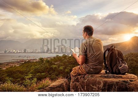 Traveler with backpack sitting on top of rock and reading a book on background of modern city. Summer vacations traveling along mountains and coast freedom and active lifestyle concept.