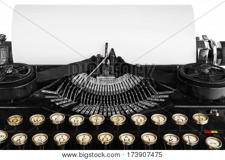 Old antique vintage portable typewriter close-up of a mechanism font and a blank sheet of paper. Antique typewriter in black with white keys of the Polish alphabet. The device isolated on a white background with light shadow and reflection.