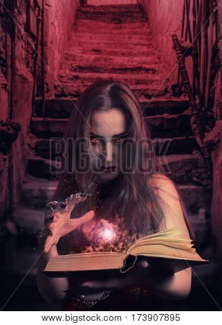 Witch holding a magic spellbook standing in the cellar photo.