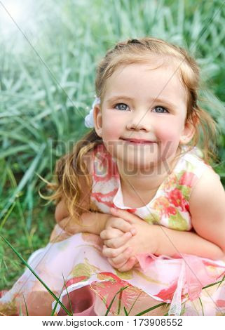 Portrait of smiling cute little girl in princess dress on summer day outdoor