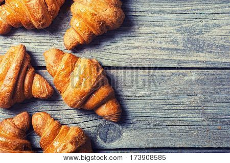 Tasty buttery croissants on old wooden table .