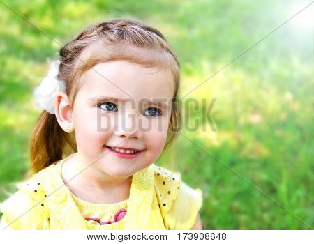 Portrait of smiling cute little girl on summer day outdoor