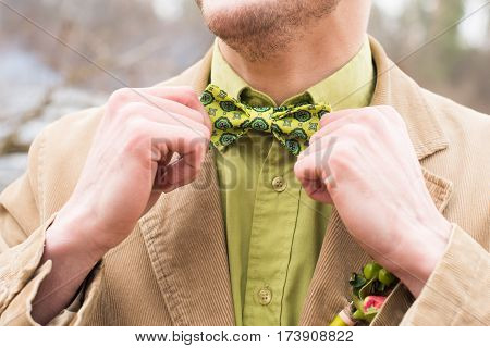 Cute stylish groom in a beige suit, green necktie and green shirt. Outdoor.
