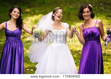 Bride And Bridesmaids In Violet Dresses Dance On The Field Holding Their Hands Together