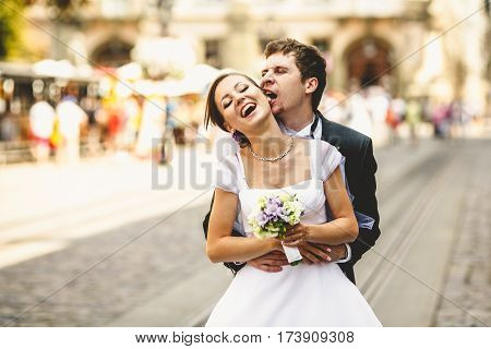 Fiance Bites Bride's Ear Holding Her In His Arms On The Street
