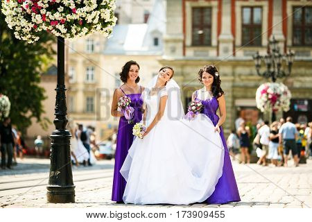 Bridesmaids lift a skirt of bride's dress up while they pose together on a street