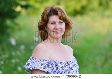 A woman in a floral dress with bare shoulders outdoors