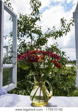 view from an open window with a bouquet on a sill