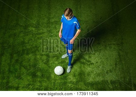 Young boy with soccer ball doing flying kick, on green studio background
