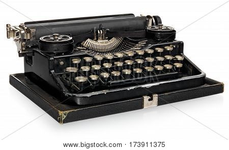 Old antique vintage portable typewriter. Antique typewriter in black with white keys of the Polish alphabet. The device isolated on a white background with light shadow and reflection.