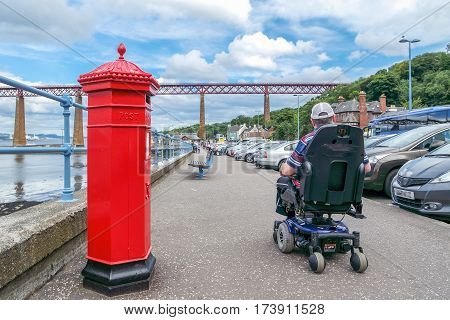 EDINBURGH, SCOTLAND - AUGUST 26 2015: Man in wheelchair passes letter box at Forth bridge