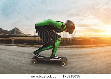 A young man in a fullface helmet and a leather suit in a special rack rides a longboard on afsaltu sunset in the background mountains and beautiful sky at high speed.