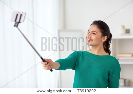 people, technology and lifestyle concept - happy woman taking picture with smartphone selfie stick or monopod at home