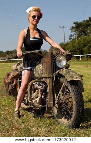 WESTERNHANGER, UK - JULY 18: A young woman dressed in period costume poses on a vintage US army motorcycle during the War & Peace show on July 18, 2013 in Westernhanger