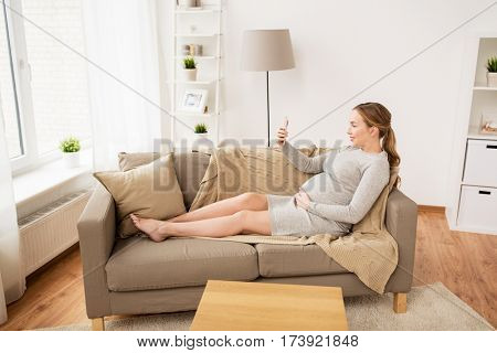 pregnancy, motherhood, technology, people and expectation concept - happy pregnant woman with smartphone taking selfie at home