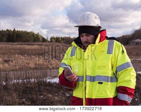 Young Engineer Working During Shift Otdoors In Helmet