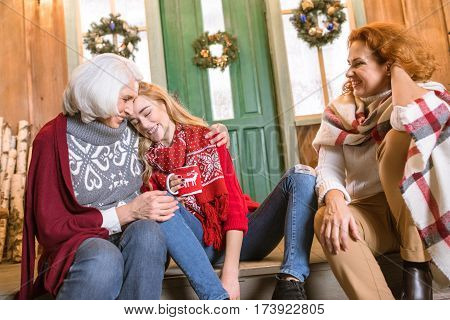 Smiling family from three generations sitting on stairs while drinking hot tea