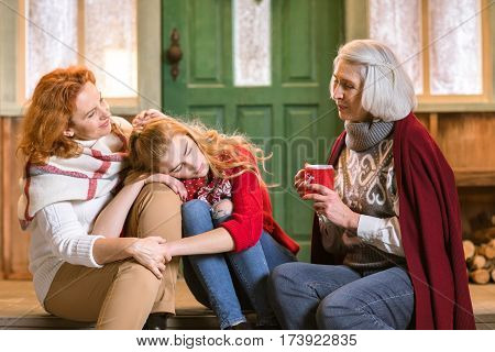 Family from three generations sitting on stairs and talking while drinking hot tea