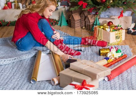 Blonde girl sitting on grey carpet and wrapping gift boxes at christmastime