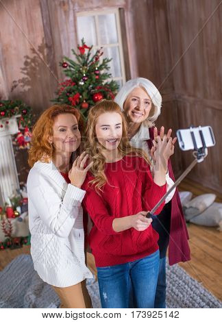 Happy family of three generations making selfie in front of decorated for Christmas fireplace