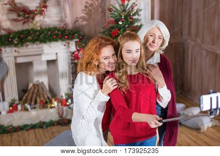 Happy family from three generations taking selfie at christmastime