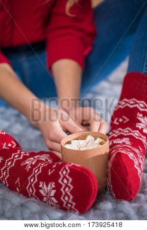Close-up view of female feet in red knitted socks and cup with hot chocolate and marshmellows