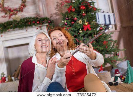 Two happy women taking selfie sitting on the floor near the Christmas tree