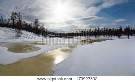 cloudy winter landscape with golden stream in South Yakutia Russia