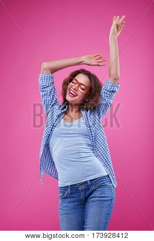 Close-up shot of young girl having fun isolated over pink background. Female in casual outfit dancing and spending time with pleasure