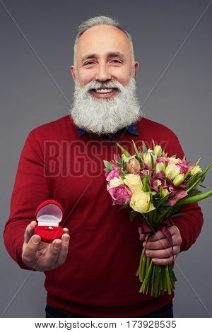 Close-up of mature bearded man making a proposal with an engagement ring and a bouquet of tulips and roses. The concept of proposal