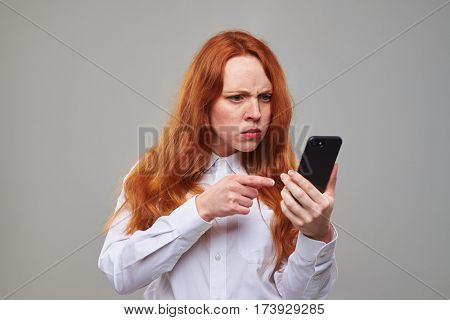 Close-up shot of an indignant redhead girl pointing at the screen of telephone. Girl isolated over background in the studio. Pretty girl with long red hair and freckles