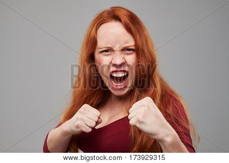 Close-up studio shot of anxious woman with red hair holding two fists isolated over gray background. Protective position