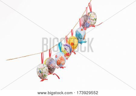 Pretty Colored Easter Eggs hanging on wire isolated on white backgroung
