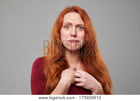 Close-up of displeased young woman with auburn hair in the studio. Offended face expression while standing isolated against background