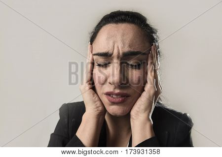 close up face of young business woman in office suit suffering migraine pain and strong headache with fingers on her tempo in business stress and work problem isolated on even background
