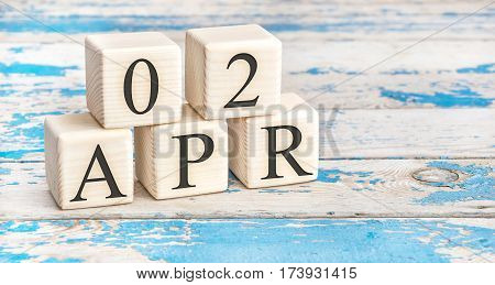 April 2nd. Wooden cubes with date of 2 April on old blue wooden background.