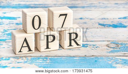 April 7th. Wooden cubes with date of 7 April on old blue wooden background.