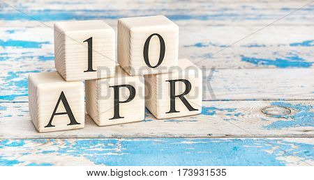 April 10th. Wooden cubes with date of 10 April on old blue wooden background.