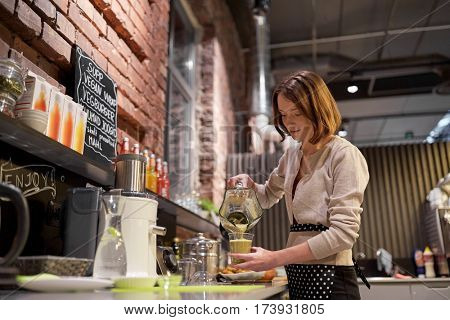 small business, people and service concept - happy woman or barmaid pouring smoothie from blender to cup at vegan cafe