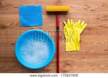 cleaning stuff, housework, housekeeping and household concept - basin with rubber gloves and swab on wooden background