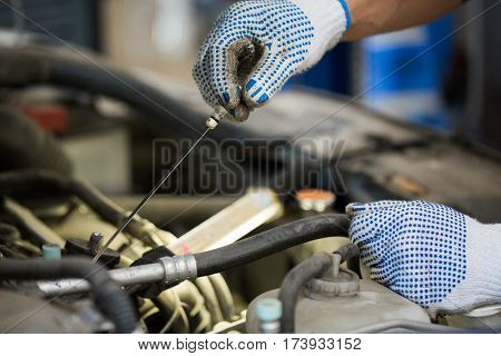 car service, repair, maintenance and people concept - auto mechanic man with dipstick and lamp checking for motor oil level at workshop
