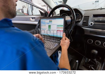 car service, repair, maintenance and people concept - mechanic man with laptop computer making system diagnostic at workshop