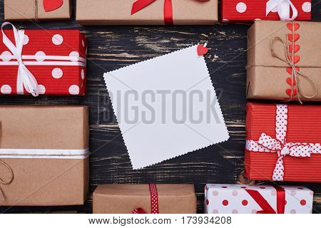 High angle of unfilled greeting card surrounded with a set of different present boxes. Concept of holiday and presents