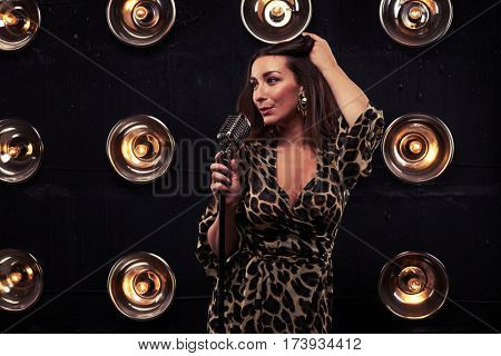 Full-length shot of stunning woman in chiffon leopard dress. Standing in studio and looking at camera. Loose Curly Hair. Pretty girl with evening makeup in eveningwear