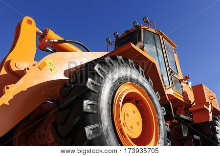 Bulldozer, huge orange powerful construction machine with hydraulic piston of scoop and black wheels, heavy industry, bottom view, blue sky on background