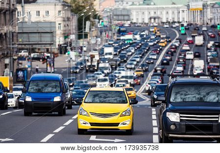 Heavy traffic on the city highway with yellow taxi car on the foreground