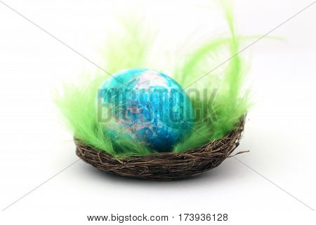 Colored easter egg in basket on white