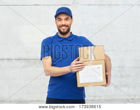delivery service, mail, people, logistics and shipping concept - happy man with parcel boxes over gray concrete wall background