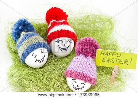 Easter eggs on green sisal. Emoticons in knitted hat with pom-poms. Handmade. White background. Isolated.