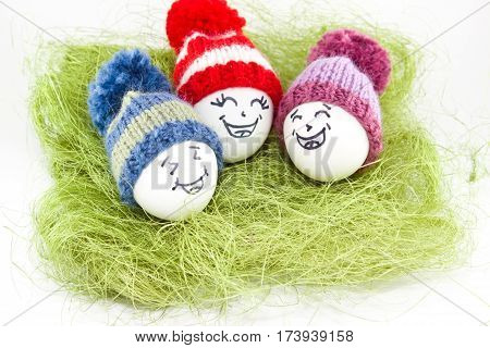 Easter Eggs On Green Sisal. Emoticons In Knitted Hat With Pom-poms. Handmade.